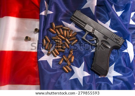 black metal Handgun with bullet and empty sleeve lying on American flag texture background Idea, symbol, concept of law on the right to bear arms, war, terror - stock photo