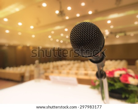 Black microphone in concert hall or conference room with de focused bokeh lights in background. Extremely shallow dof. Filtered process. - stock photo