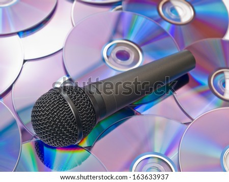 Black microphone on the background of the disks - stock photo