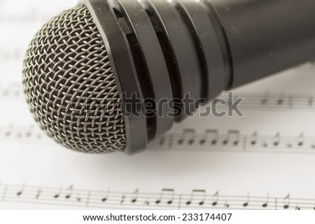 Black microphone over musical score, horizontal image - stock photo