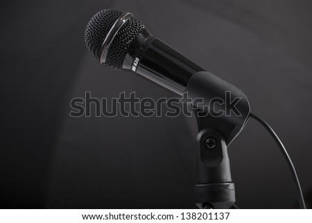 black microphone with cable isolated on a black - stock photo