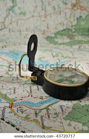 Black, military compass on the detailed map. - stock photo