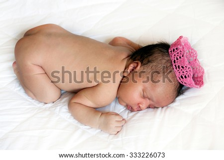 Black mulatto newborn baby sleeping on a bed in a crown - stock photo