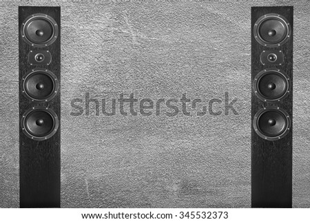 Black music speakers on gray wall background. Element of sound design - stock photo
