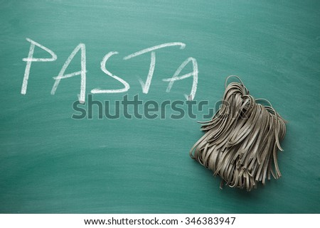 black noodles with squid sepia ink on chalkboard - stock photo