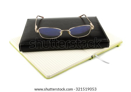 Black notebook and glasses on a white background - stock photo