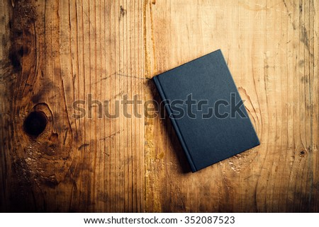 Black notebook on wooden office desk, top view - stock photo