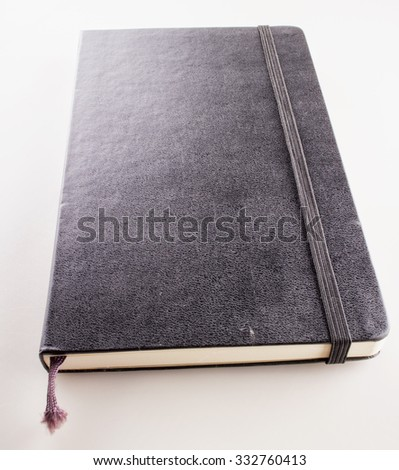 Black notebook over white background, square image - stock photo