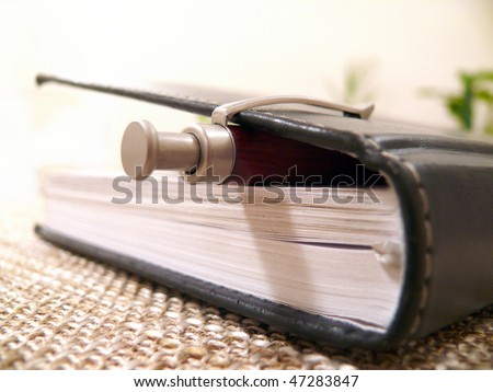 black notebook with a pen - stock photo