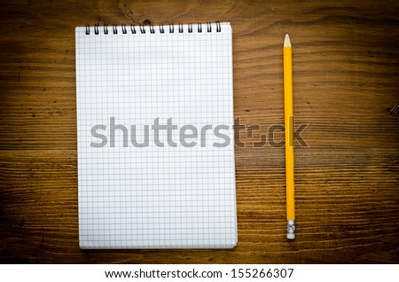 Black notebook with pencile on a wood background - stock photo