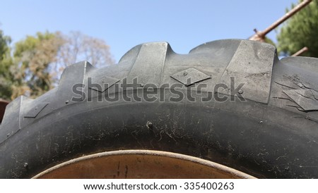 Black Off-the-road tire sidewall with over-sized tread lugs along its shoulder - stock photo