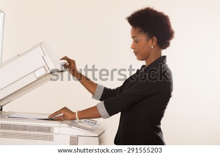 Black office woman lifting up lid of copy machine and holds a paper in other hand - stock photo
