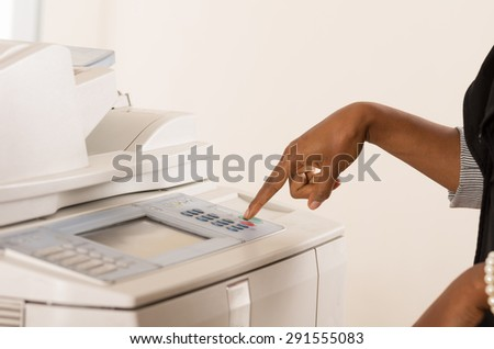 Black office womans hand pressing buttons on a copy machine - stock photo