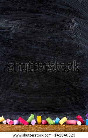 Black old empty chalkboard for copy space with colorful pieces of chalk - stock photo