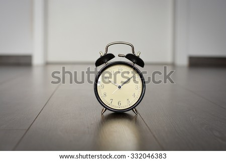 Black Old or classic alarm clock on wooden floor suggesting deadline concept - stock photo