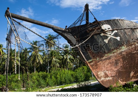 black, old, rusty, stranded pirate ship with a white skull and crossed bones and a tropical forest with coconut palm trees in the background - stock photo