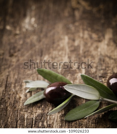Black olive branch with leaves and olives lying on a textured weathered wooden table surface with copyspace - stock photo