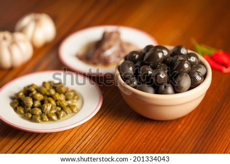 black olive (oliu ) and other pizza raw materials on a wooden table - stock photo