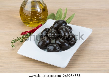 Black olives in the bowl on wood background - stock photo