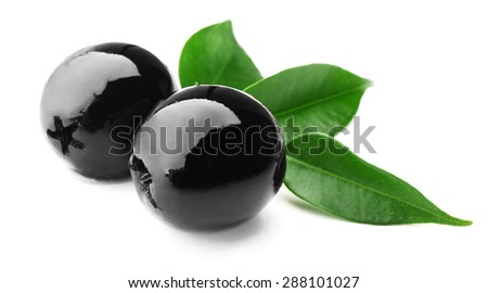 Black olives with green leaves isolated on white - stock photo