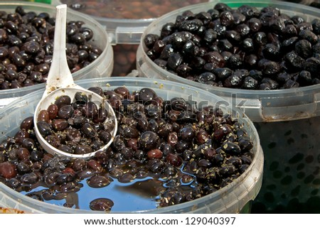 Black olives with spoon at the local market - stock photo