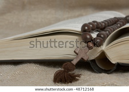 black opened bible and wooden cross on rustic canvas - stock photo