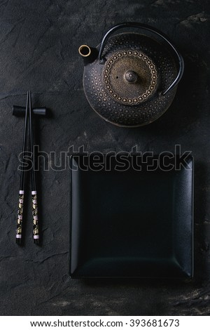 Black painted chopsticks on chopsticks rest, empty square plate and iron teapot over black textured surface. Flat lay. - stock photo