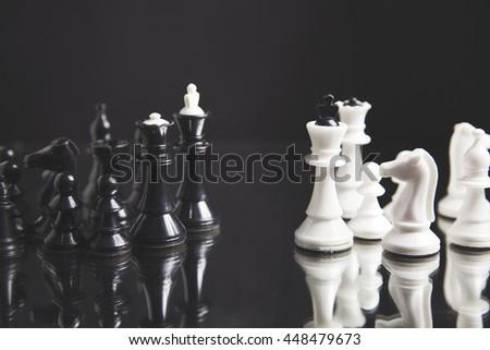 black pawn among white chess on black background - stock photo