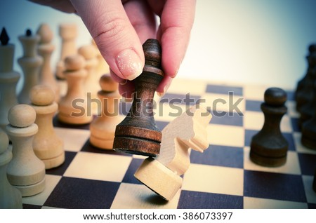 Black pawn beats white horse on chessboard. Prostrate chess knight. Pawn holding a woman's hand. Selective focus, close up view. Vintage toning. - stock photo