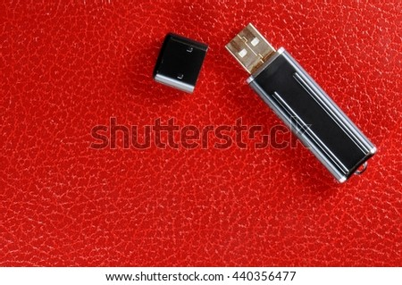 Black Pen Drive on red leather background - stock photo
