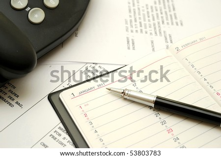 Black pen on planner with business documents in background, signifying concepts such as office and business, planning for the new year, financial budget and work related objects - stock photo