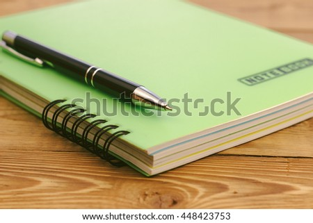 black pen on the closed notebook lying on a wooden table - stock photo