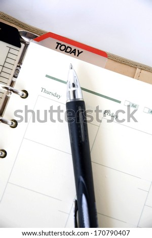black pen point to date today on agenda - stock photo