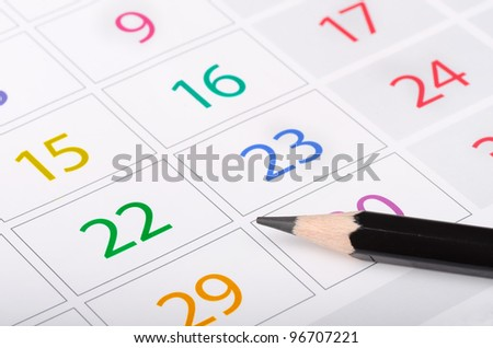 Black pencil on calendar page with colorful dates - stock photo