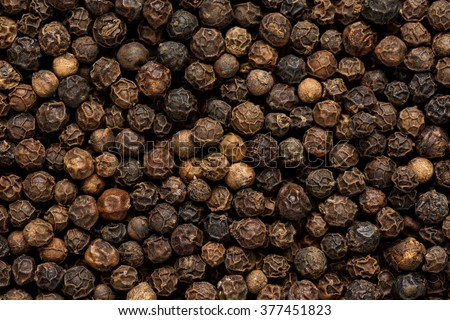 Black pepper grains as background close up - stock photo