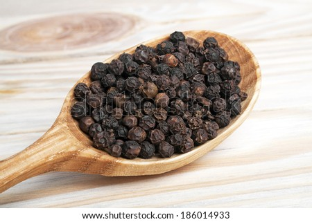 Black pepper in spoon on a wooden background - stock photo