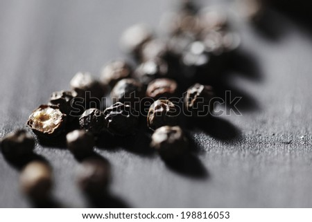 Black peppercorns on wooden table - stock photo
