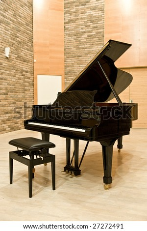 black  piano and a chair in sound recording studio - stock photo