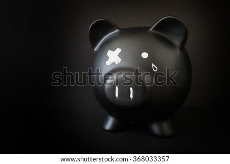 Black piggy bank with a tear and X'd out eye,  taking a beating - stock photo
