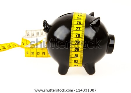 Black piggy bank with measuring tape on white background - stock photo