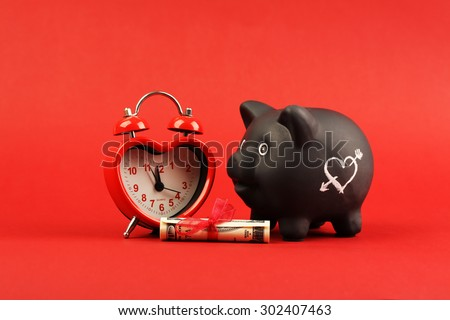 Black piggy bank with white heart and heart alarm clock and gift of money american hundred dollar bills with red ribbon standing on red background - stock photo