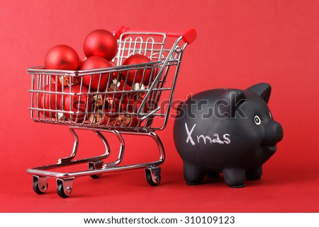 Black piggy bank with white text Xmas and full shopping basket of red matt and glossy christmas balls on red background - stock photo