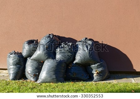 Black plastic bags in harsh light with leaves trash collected in autumn - stock photo