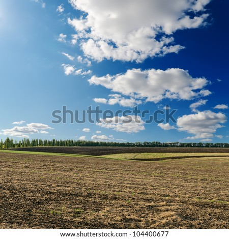 black ploughed field under deep blue sky with clouds - stock photo