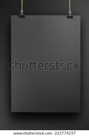 Black poster on a rope. Sheet of paper hangs on two black binder clips. - stock photo