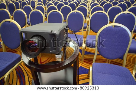 Black projector on background of rows of yellow-blue chairs in bright conference hall - stock photo