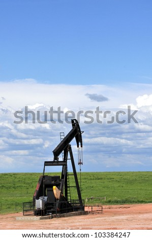 Black pump jack on a green prairie with a large copy space, vertical - stock photo
