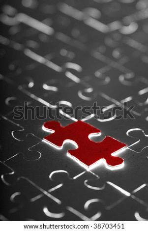 black puzzle with one red piece - stock photo