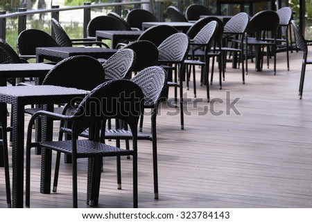 black rattan table and chair on the terrace at the patio - stock photo