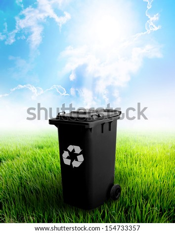 Black Recycle Bin With Landscape Background. - stock photo